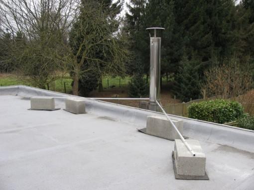 Twee aluminium staven vastgevezen aan vier betonblokken houden de schoorsteen op zijn plaats.