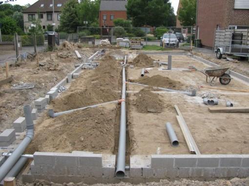 Vervolgens de boel ingraven, zorgen dat er een lichte afloop is (1-2 cm/m), en de laatste stukjes muur dicht metsen.