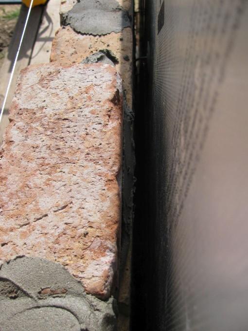 De mortel met de truweel tegen de steen smeren.  Opletten dat er geen mortel naar beneden valt in de spouw.