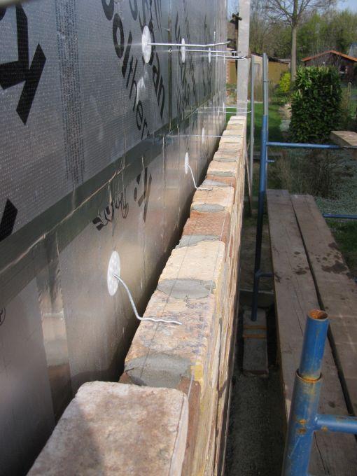 Gaten voor die rozetten worden met een 9,5 mm steenboor geboord.  De rozetten er in kloppen en dan de spouwankers er in kloppen.  Ik wacht met een rij spouwankers er in te koppen tot ik bijna aan die rij stenen ben.  Anders zit ik nogal veel met mijn koppeke tegen die spouwankers.