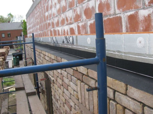 Nog twee rijen boven de streklaag gemetst, en dan waterkerende laag boven de vensters en boven de doorvoer van de dampkap aan de isolatie gelijmd.