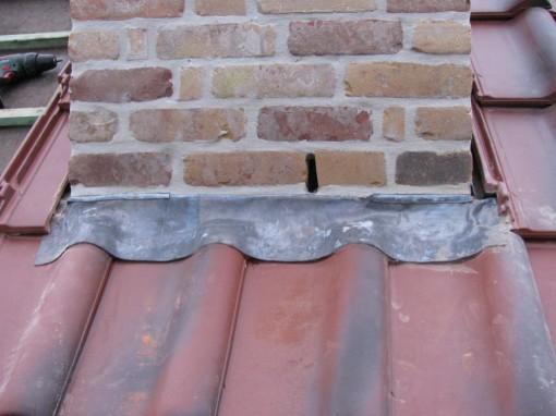 De voorkant van de schoorsteen.  Redelijk wat geklop met een rubber hamer om dat lood in de vorm van de pannen te krijgen.  En het is vastgelijmd aan de pannen.