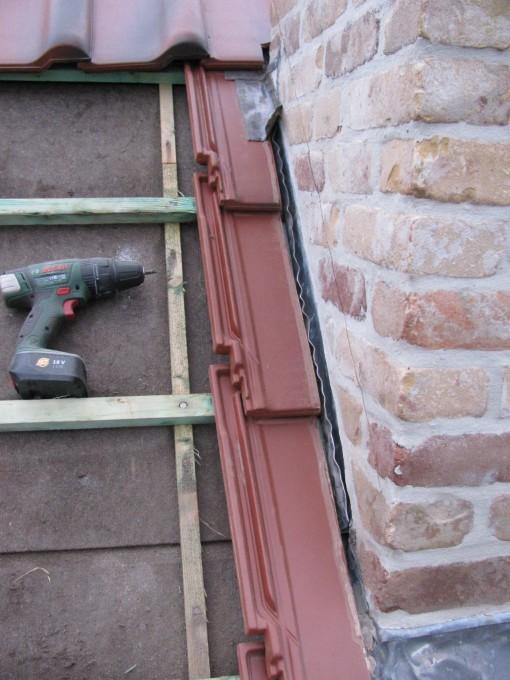 Het te lage lood in een gootje, en bovenaan ervoor gezorgd dat het water van achter de schoorsteen via de pannen afgevoerd wordt.