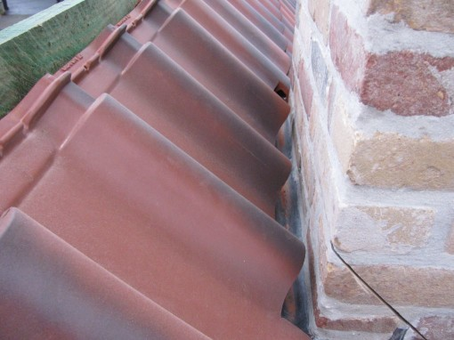 De achterkant van de schouw.  Daar zit het lood onder de pannen en vormt daar een goot die uitkomt aan de zijkanten.