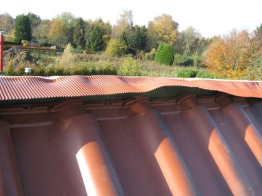 Eenmaal op beide dakvlakken de bovenste twee rijen pannen er liggen, kan de nok gelegd worden.  Eerst wordt aluminium eterrol op de nokplank genageld.