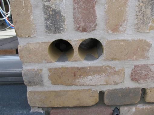 Gaten boren, stofzuigen en uitblazen met compressor. Vervolgens met chemisch anker de bakjes in de gaten bevestigen.