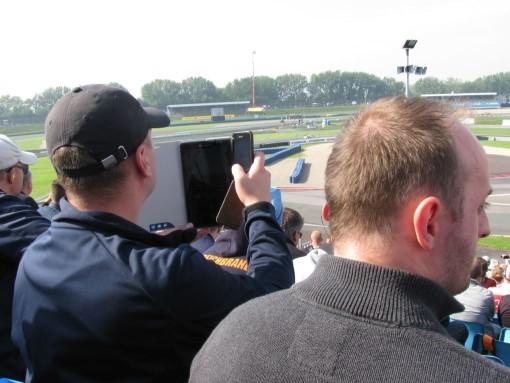 """We zijn ook naar een DTM (""""Duitse Toerwagen Masters"""") geweest.  Niet echt mijn ding, maar wel eens leuk om mee te maken.  Echte fans (zoals die op de foto) filmt zelfs met zijn tablet EN gsm de doorgang na de start in de eerste bocht, om alle mogelijke botsingen vast te leggen..."""