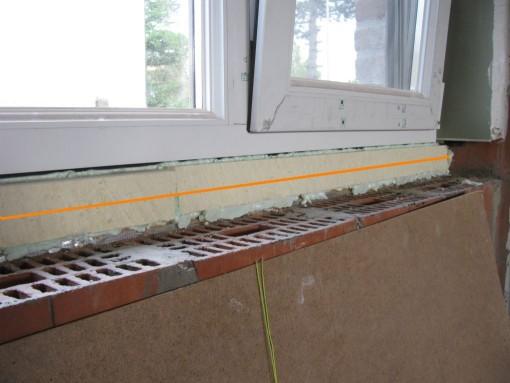 Ik heb de strook isolatie vast gespoten met PUR en dan een horizontale snede gemaakt die 1 cm diep ging, zodat mijn vensterbank net onder het raamkader komt.  Vervolgens de vensterbank plaatsen op spieën zodat die die waterpas zit en 0,5 cm onder het vensterkader zit.  De achterkant heb ik onderaan opgespoten met PUR, de rest met mortel opgevuld. (sorry, foto vergeten)