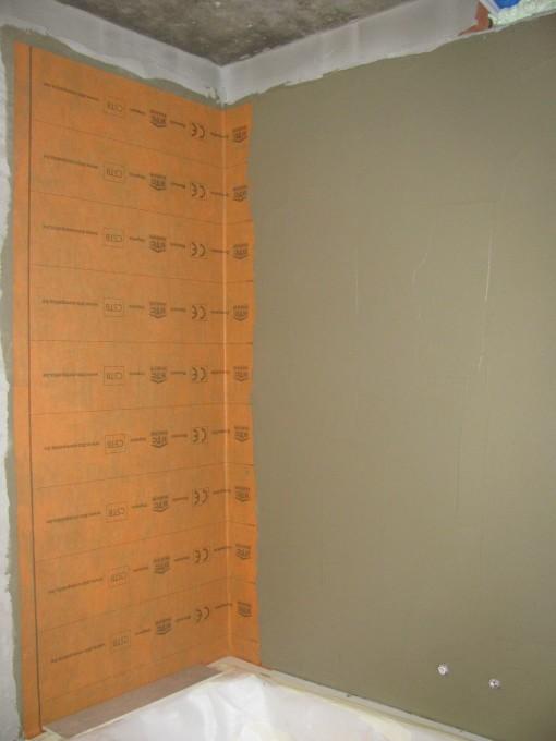 tegellijm tegen de muur smeren, en daartegen Kerdi doek plakken. Dit zorgt ervoor dat er geen vocht in de muur kan trekken bij het douchen.