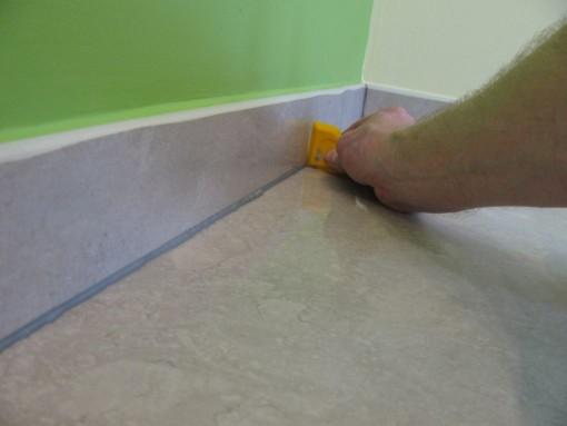 Afstrijken met een hoekprofiel.  Omdat de tegels en plinten nat zijn, blijft er geen silicone kleven aan de tegels.