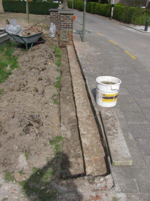 Het muurke afgebroken tot een paar stenen onder het voetpad.