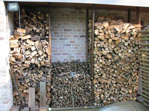 Al een hele boel brandhout gestapeld.  Links droog hout van afbraak, midden dunne takjes voor aansteken kachel, rechts de recent omgezaagde boom in stukjes.